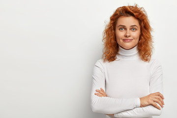 Portrait of good looking redhead woman looks with little smile, has calm face expression, keeps arms folded, wears white turtleneck, poses alone, listens pleasant comments, isolated on white wall