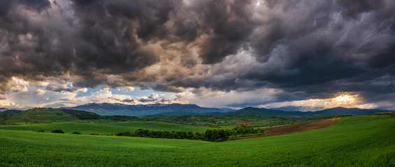 Türaufkleber Wiesen / Sumpfe Panoramic view of uneven green agriculture fields in the foreground, distant mountain range in the background, and heavy stormy overcast dramatic clouds in the sky