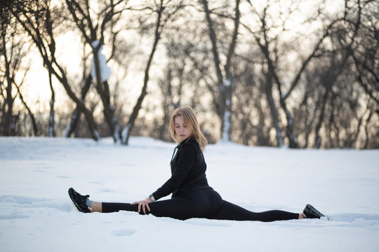 Young caucasian female blonde in leggings stretching exercise sitting on a string at open air in snowy forest. fit and sports lifestyle
