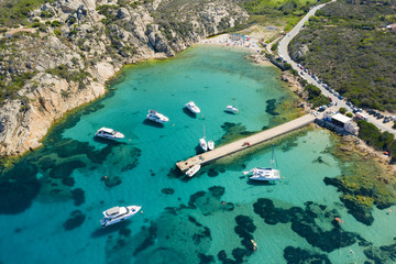 Fototapete - View from above, stunning aerial view of luxury yachts and boats floating on an emerald green bay of water in Sardinia. Maddalena Archipelago National Park, Sardinia, Italy...