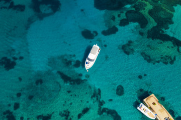Fototapete - View from above, stunning aerial view of a luxury yacht floating on an emerald green bay of water in Sardinia. Maddalena Archipelago National Park, Sardinia, Italy...