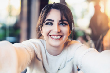 Smiling girl taking selfie with her hands for social networks while sitting in cafe. Portrait of young woman photographing herself