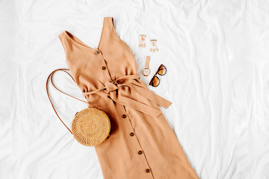 Beige dress with bamboo bag and accessories on white bed. Women's stylish autumn or summer outfit. Trendy clothes. Flat lay, top view.