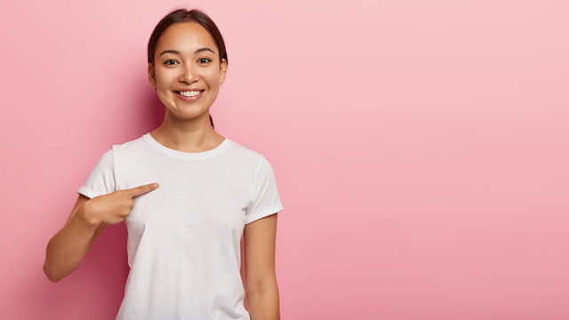 Happy smiling Asian woman points at plain white t shirt, shows copy space for your slogan or promotion, has natural dark hair, satisfied expression, models over pink background. Clothing and advert