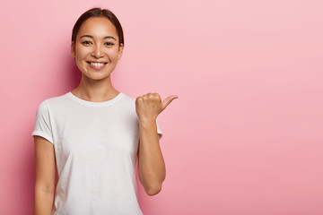 Horizontal shot of happy young Asian woman points away on copy space, demonstrates something good,...