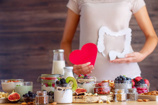 Female is holding figures of heart and intestines. Summer breakfast with organic yogurts fruits, berries and nuts. Nutrition that promotes good digestion and functioning of gastrointestinal tract.