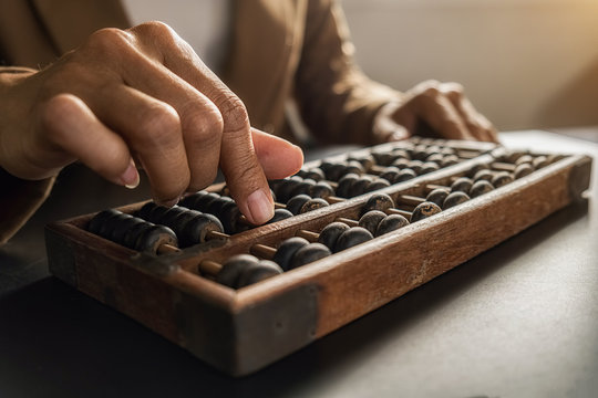 Asian woman hands accounting with old abacus. Financial design concept.