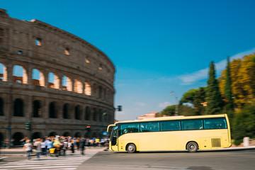 Rome, Italy. Colosseum. Yellow Bus Moving On Street Near Flavian Amphitheatre. Famous World UNESCO Landmark