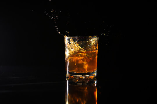 Shot of whiskey with splash on black background
