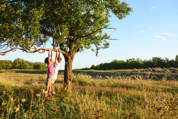 Brother And Sister Together Forever. Children play while climbing a tree at sunset.