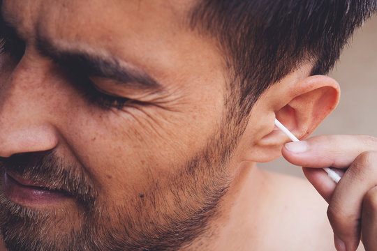 Man about to clean his ears using Q-tip cotton swab. Hygiene essentials concept. Removing wax from ear.
