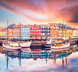 Breathtaking beautiful scenery with boats in the famous Nyhavn in Copenhagen, Denmark at sunrise. Exotic amazing places. Popular tourist atraction.