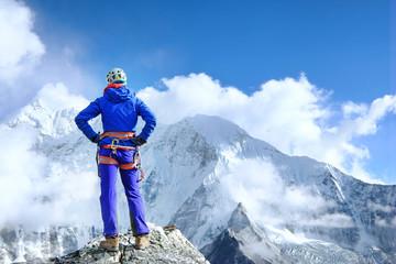 Climber reaches the summit of mountain peak enjoying the landscape view. Fototapete