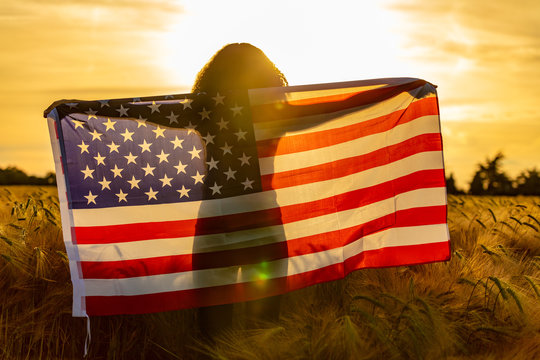 Girl Teenager Wrapped in USA Flag in Field at Sunset