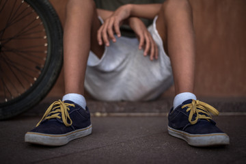 Close up view of legs of a trendy boy relaxing alone sitting near his bicycle. Feet with skater sneakers of a young man with bmx. Portrait of a kid with rapper hat. Youth loneliness generation concept