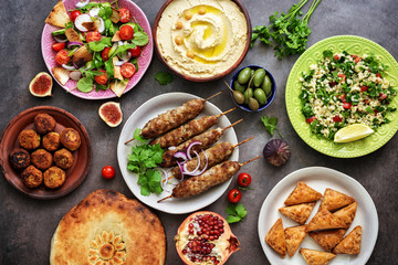 Assorted variety of Arabic and Middle Eastern food on a dark rustic background. Hummus,tabbouleh salad, salad Fattoush,pita,meat kebab,falafel,baklava. Set of Arabian dishes.Top view.