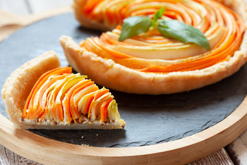 Homemade vegetable tart with cabbage and carrot decorated with basil on old wooden table