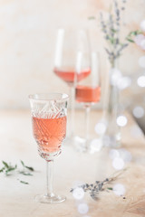 Different shapes of glasses of rose wine on light background.