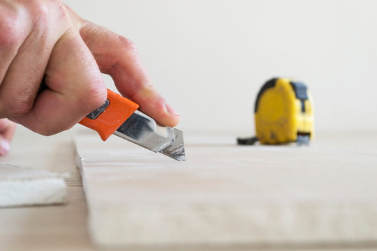 Cutting a sheet of drywall with a knife.
