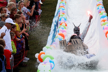 Participants slide down along a chute to cross a pool of water and foam during the festival near Krasnoyarsk