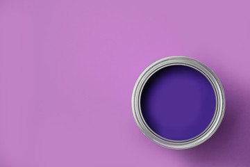 Open can of paint on violet background, top view. Space for text