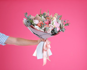 Man holding beautiful flower bouquet on pink background, closeup. Space for text