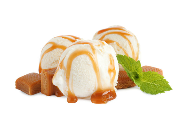 Delicious ice cream with caramel sauce, candies and mint on white background