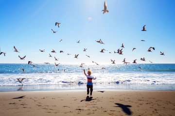 Happy and free boy on the beach with seagulls Wall mural