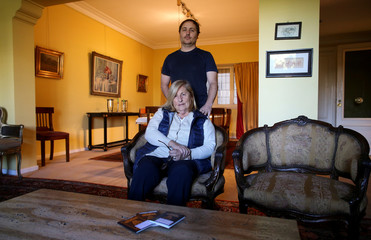 Guillermo Galia poses for a picture with his mother Slivia at his home, in Buenos Aires