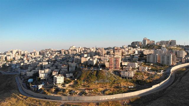Israel Palestine divided by security fence in Jerusalem aerial view Drone flight view of east Jerusalem security wall divide between Israeli and Arab neighborhood  Anata and pisgat zeev, Israel