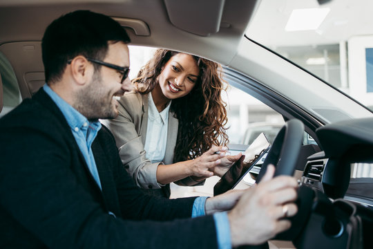 Happy middle age businessman buying new and luxury car. Beautiful female dealer helps him to make right decision.