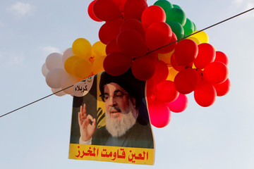 Balloons with a picture of Lebanon's Hezbollah leader Sayyed Hassan Nasrallah hang in the air during a rally marking the anniversary of the defeat of militants near the Lebanese-Syrian border, in al-Ain
