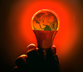 The picture of the world is in a light bulb. The concept of using electricity that causes global warming