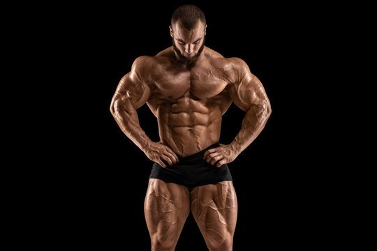 Muscular man showing muscles, isolated on the black background. Bodybuilder male naked torso abs