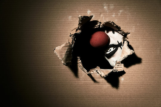 A creepy scary vampire clown with a red nose shows his fangs through torn cardboard. Halloween theme with blank space on the left.