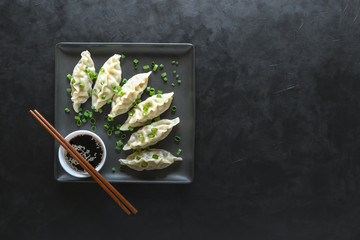 Homemade Meat Dumplings with soy sauce on black plate.