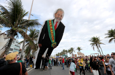 People hold an inflatable doll of former Brazilian president Luiz Inacio Lula da Silva ahead of the demonstration to demand more protection for the Amazon rainforest in Rio de Janeiro