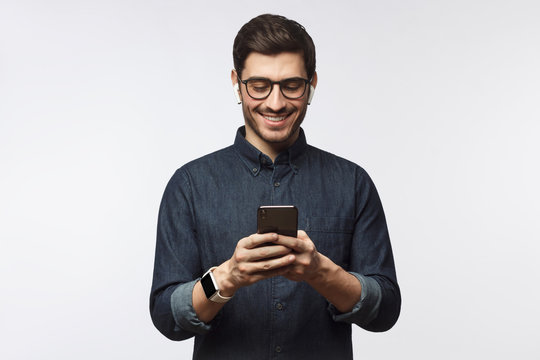 Man looking at phone, standing isolated on gray background