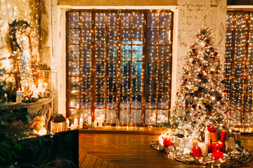 warm cozy magic evening in luxury old Christmas living room fairy tale interior design, fireplace, windows, Xmas tree decorated by lights, gifts, candles, lanterns, garland lighting.New year holiday