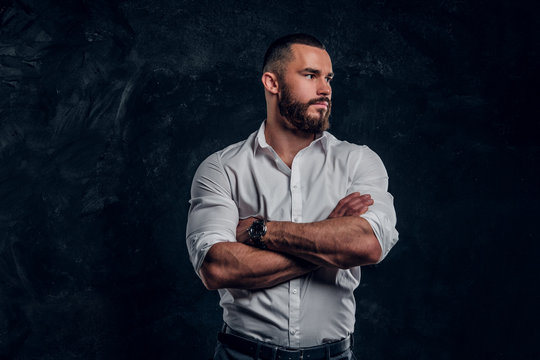 Sucessful bearded businessman in white shirt is posing at dark photo studio.