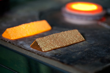 closeup picture of ingots of melt gold, hot shiny metal bars on table and fire furnace on background