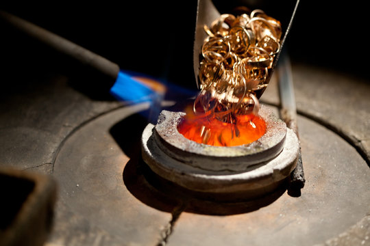 pieces of gold loaded into furnace for melting