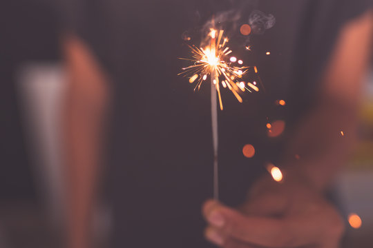 young girl burning sparkler in hand