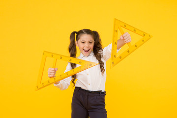 Exploring the properties of triangles in the lesson. Cute girl holding triangles for lesson in...