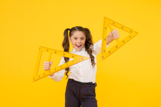 Exploring the properties of triangles in the lesson. Cute girl holding triangles for lesson in technical drawing. Little child ready for geometry lesson. Using measuring instruments at school lesson