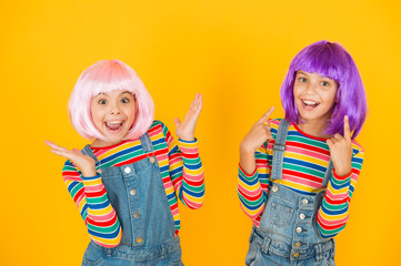 Happy little girls. Anime fan. Cheerful friends in colorful wigs. Anime convention. Anime cosplay...
