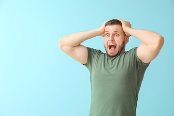 Man having panic attack on color background