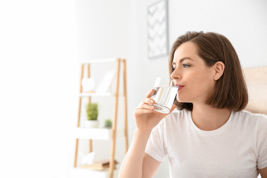 Morning of beautiful young woman drinking water in bedroom