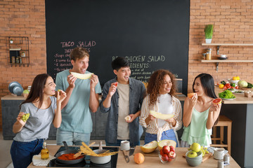 Happy friends eating fruits together in kitchen