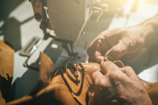 Working process of leather craftsman. Tanner or skinner sews leather on a special sewing machine, close up